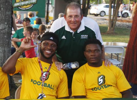 """Frank Scelfo, football head coach, poses with some players at """"Hot August Night"""" in downtown Hammond."""