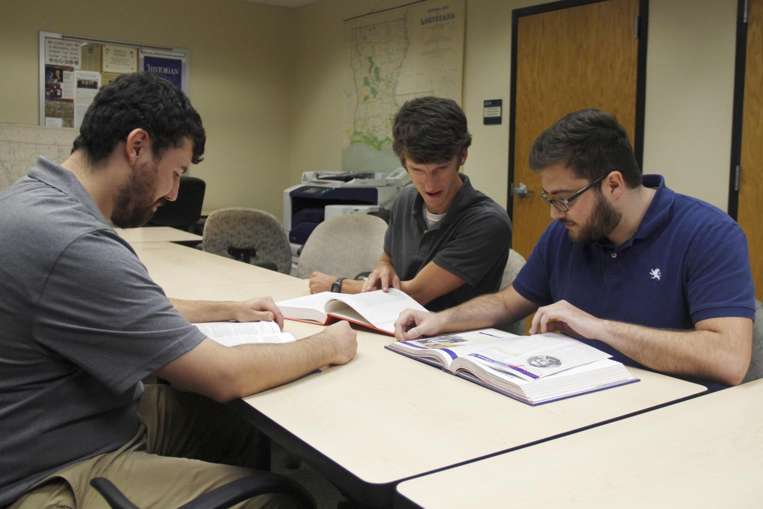 Chad Duffaut, Brody Simmons and Everett Paretti, all graduate students in history, check out some textbooks. Students may be fascinated by the classes or find their second home in the Department of History and Political Science .