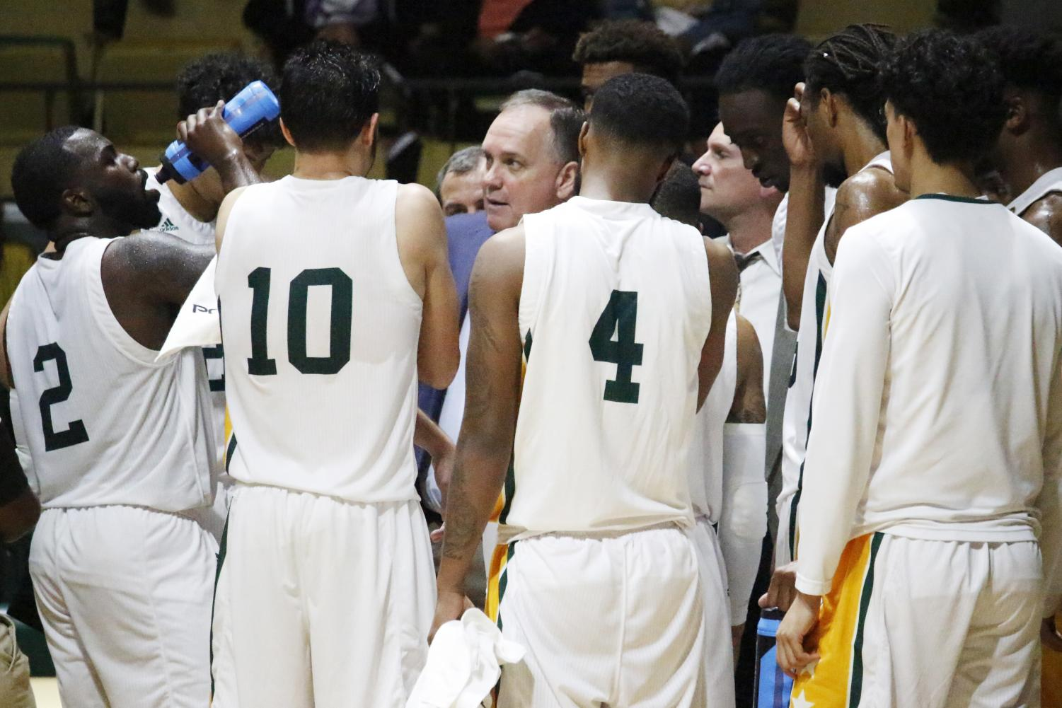 Jay Ladner, head coach of men's basketball, talks to his players about their game plan. Games include coaches giving their players a pep talk to rally morale and win the match.