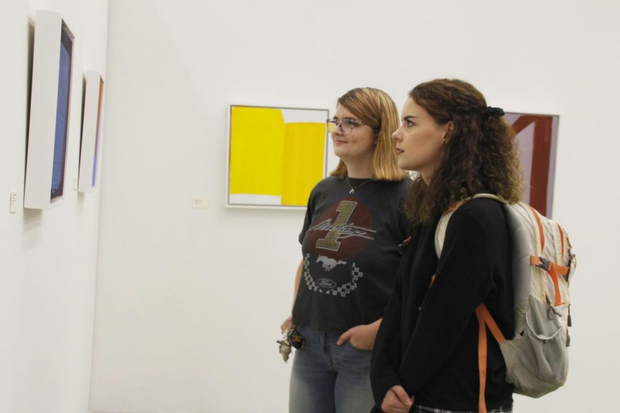 """Leia O'Connell, a senior kinesiology major, and Katherine Davis, a senior sociology major, check out the abstract artwork for the Contemporary Art Gallery's opening reception of the """"Real to Not Real"""" exhibition."""