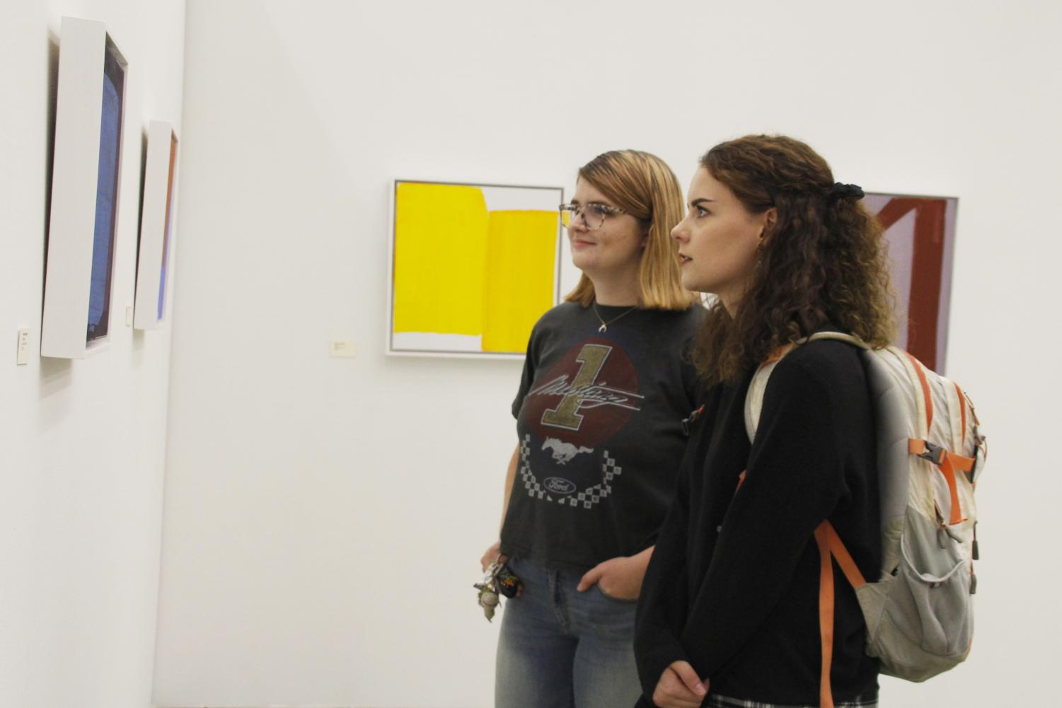 "Leia O'Connell, a senior kinesiology major, and Katherine Davis, a senior sociology major, check out the abstract artwork for the Contemporary Art Gallery's opening reception of the ""Real to Not Real"" exhibition."