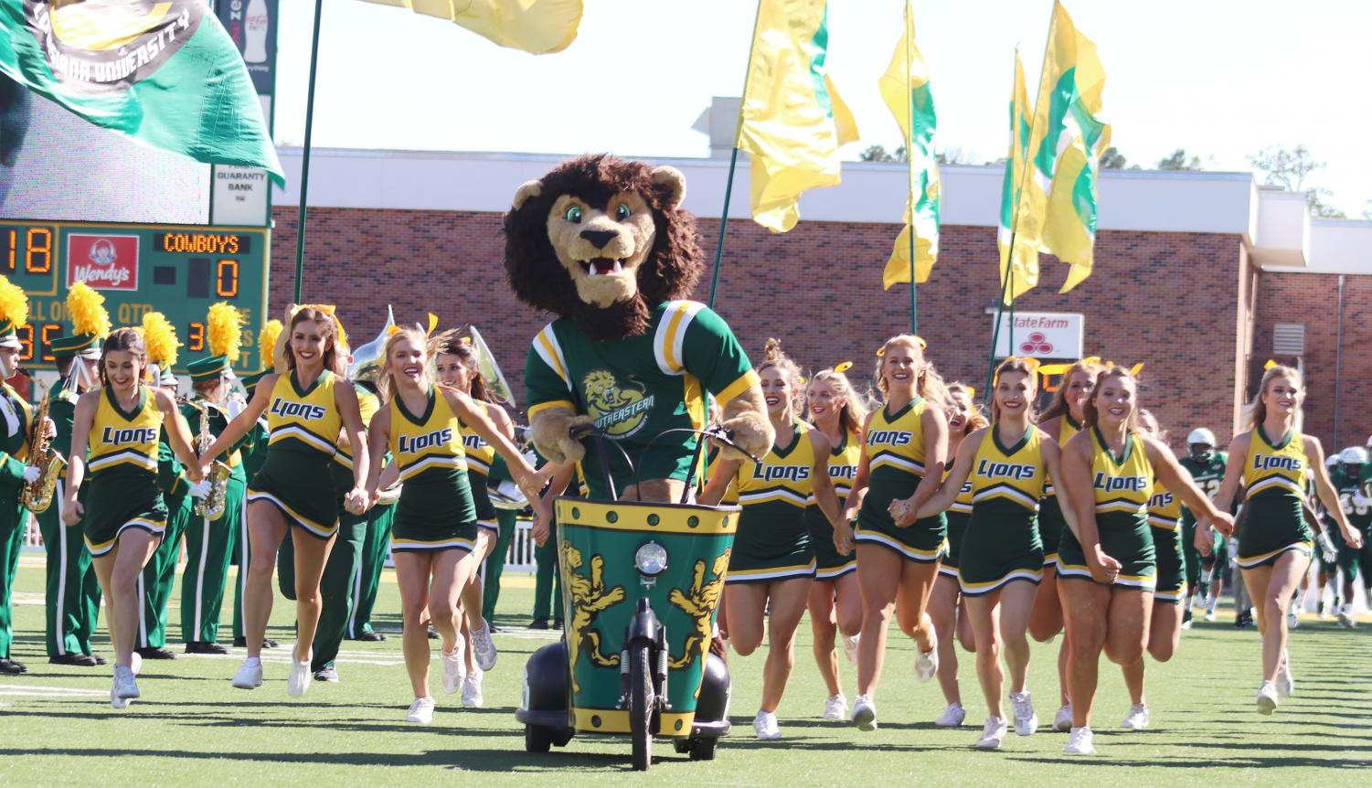 "Roomie rides out with the university cheerleaders before a home football game. Besides the spirit squads and mascot, home football games also include sponsorships like ""Our Mom of the Game."""
