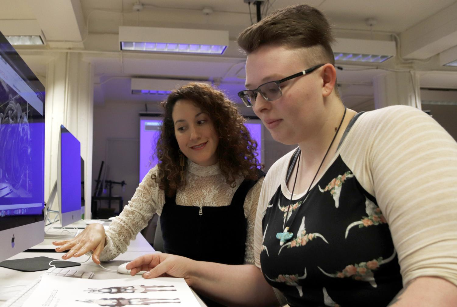 Cristina Molina, assistant professor of new media and animation, shows Sierra Arbaugh, a sophomore art major, works by Louise Bourgeois in class. Inspiration from her mom, aunts and grandmothers helped Molina grow in her artistic endeavors.