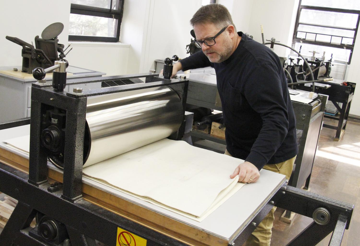 Ernest Milsted uses one of the printmaking machines located in Clark Hall room 303. His passion for photography, printmaking and the creativity of his students serves as an inspiration for his art.