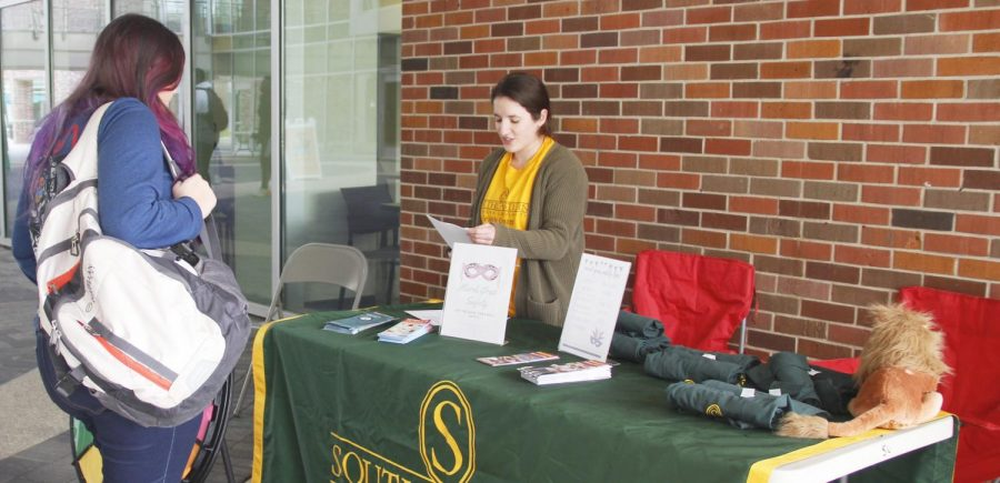 Eryn Brannagan, a senior health education and promotion major, offers students tips about safety during Mardi Gras in the Student Union Breezeway on Feb. 25. The informational session included a game where students could answer questions about safety and win a T-shirt.