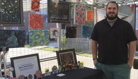 Dr. Marc Settembrino, assistant professor of sociology,  poses with his artwork. Through the Hammond Art Guild, Settembrino advertises his art to the community.