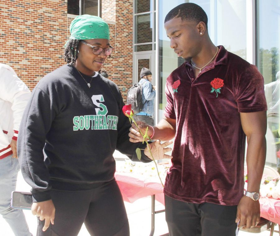 Members of Kappa Alpha Psi Fraternity, Inc. handed out roses and treats to women passing by in honor of Women's History Month.