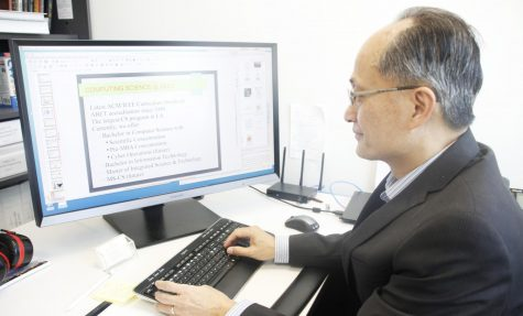 Dr. Quoc-Nam Tran, head of the Department of Computer Science, prepares a PowerPoint presentation about the importance of the computer science major for incoming freshmen. The university's Department of Computer Science graduates the most computer science students in the state.