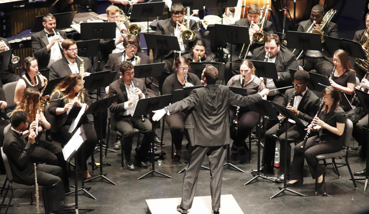 Derek Stoughton, conductor of the Wind Symphony, directs the performers in a concert that calls back to the medieval renaissance. The concert was the symphony's last production of the season.
