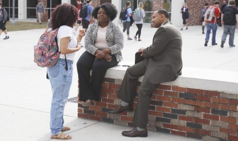 Eric Summers, vice president for student affairs, and Angela James, director of the Office of Disabilities Services, chat with a student outside the War Memorial Student Union.