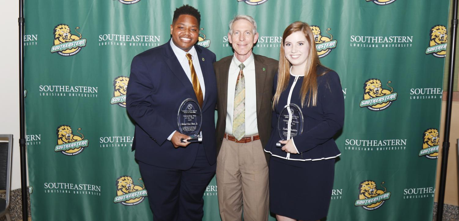 During DSA convocation, Richard Davis Jr., a senior middle school education major, left, was named 2019 Man of the Year, and Karley Bordelon, a junior social studies major, right, was named 2019 Woman of the Year.  The two honorees pose with Dr. John L. Crain, university president.