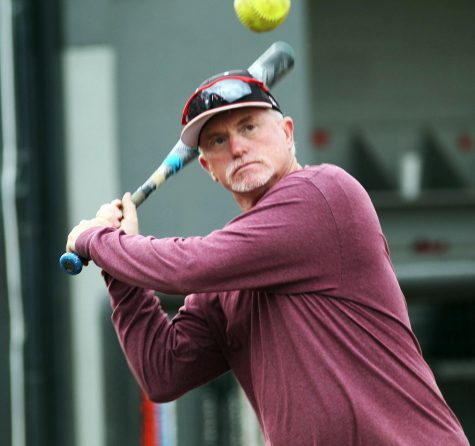 Jack Byerley, assistant softball coach, winds up the bat at practice. Byerley, armed with decades of coaching experience from schools around the nation, has recently joined the Lions softball coaching staff.
