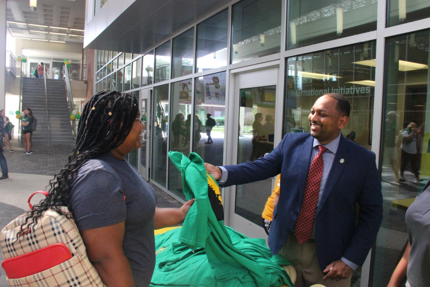 Dr. Eric Summers, vice president for student affairs, hands out T-shirts to students in the Student Union Breezeway. The university marked the beginning of Homecoming Week on Monday, Oct. 7.