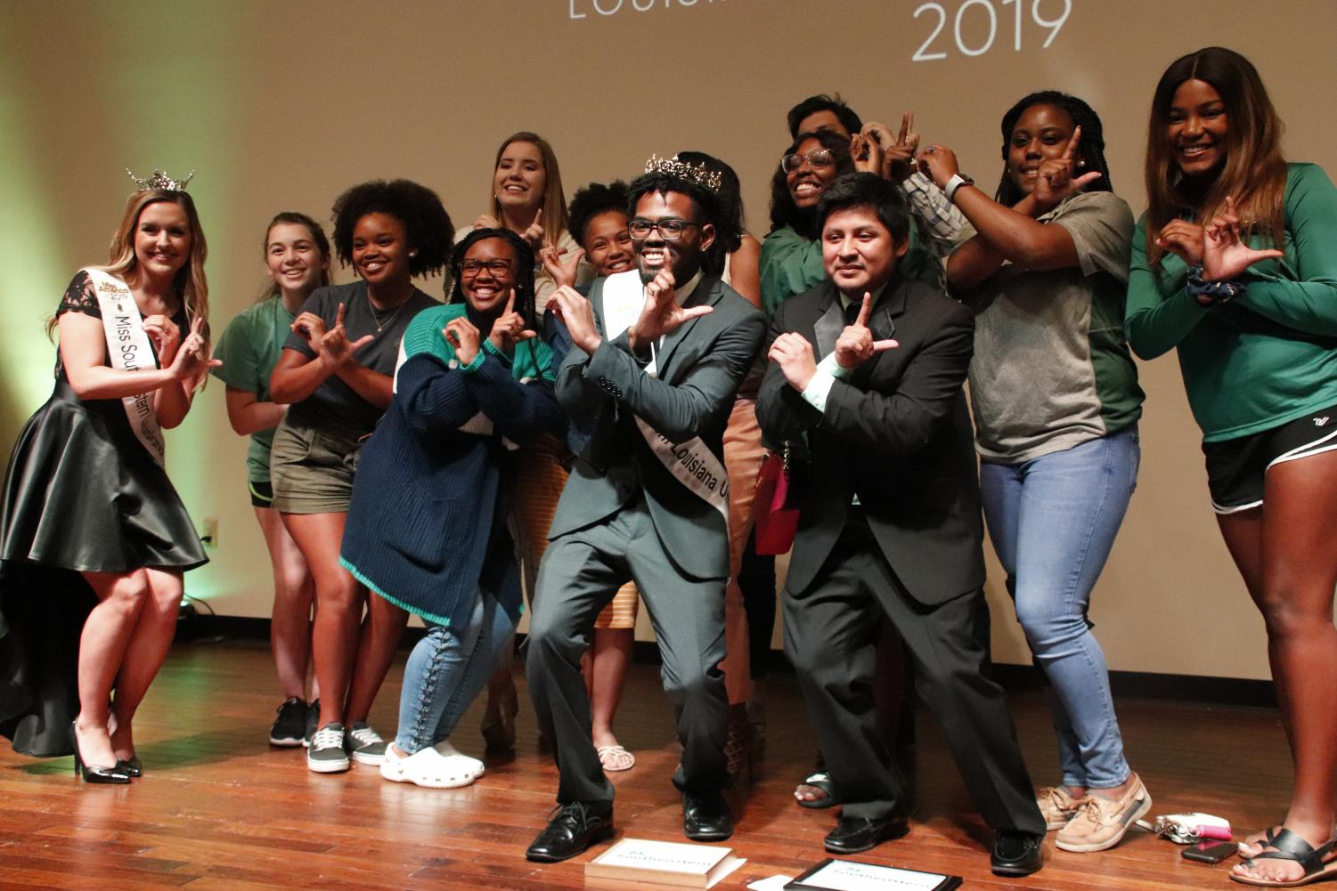 """Brian Williams, a senior communication major, poses for a picture with Miss Southeastern Louisiana University 2019 Chelsey Blank and orientation leaders after winning the competition. Williams played musical instruments for his talent competition, and won the """"Best Hair Award."""""""