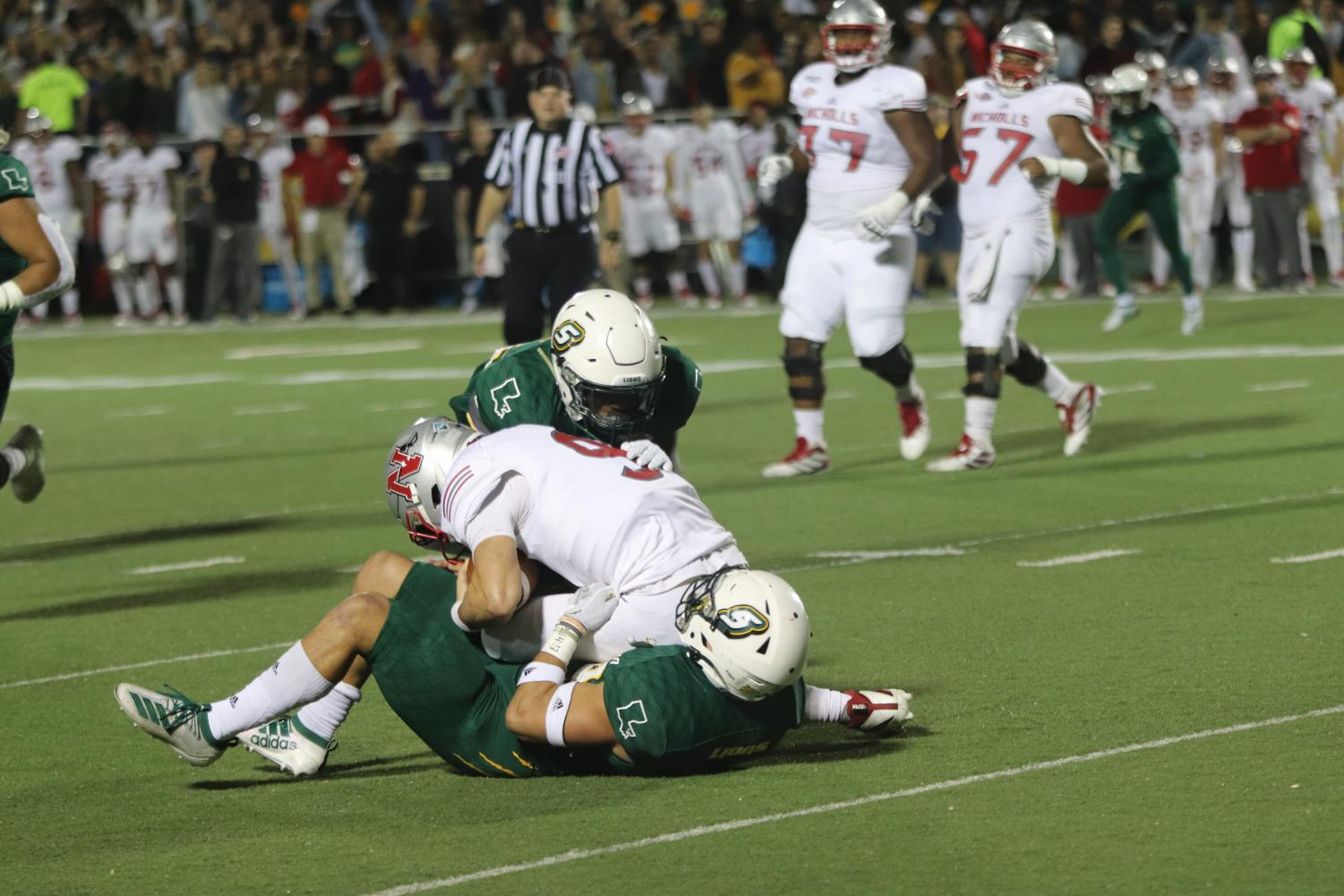 Linebackers Alexis Ramos and Joshua Carr sack Nicholls State quarterback Chase Fourcade. Ramos was ejected in the third quarter due to a targeting penalty.