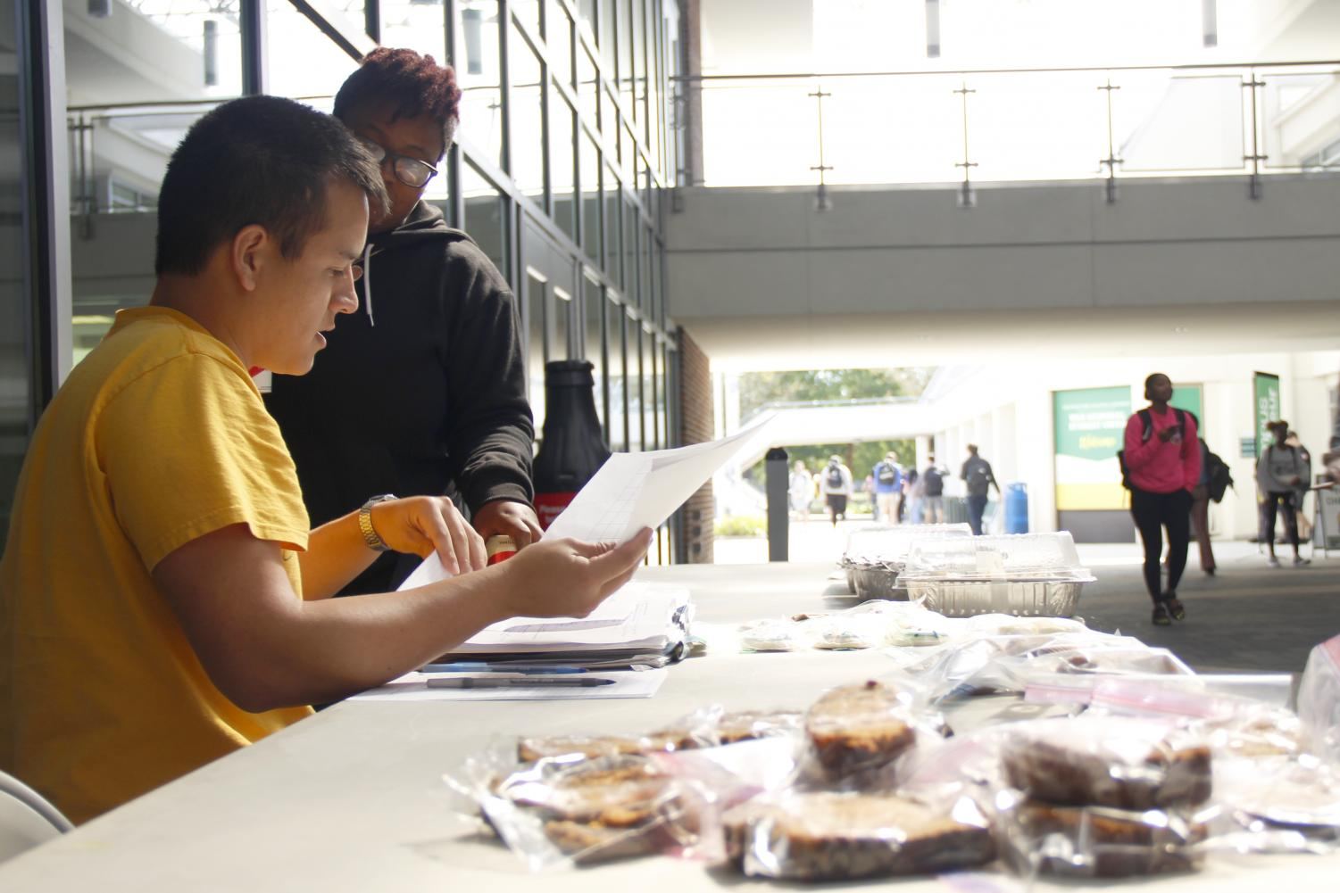 Jean Paul Templet, a sophomore biological sciences major, and Amanda Scott, a junior social work major, discuss their bake sale plans to raise money for their organization and spread awareness on mental illness.