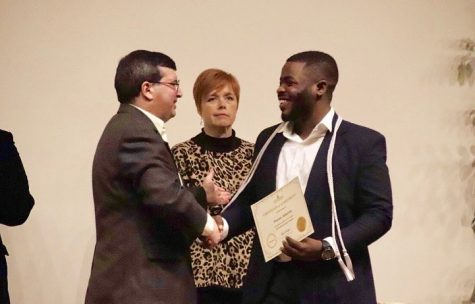Fawaz Adesina, a senior physics major, is awarded with his Honors Cord after being recognized for completing his Honors Diploma. His senior project was titled