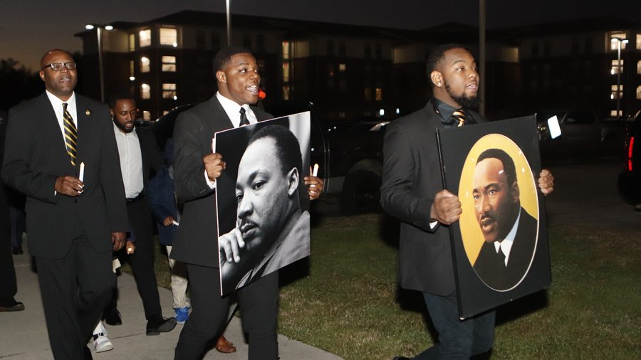 Bomani+Brown%2C+member+of+the+Kappa+Nu+chapter+Alpha+Phi+Alpha+Fraternity%2C+Inc.%2C+and+Larry+Banks%2C+Vice+President+of+the+Kappa+Nu+chapter%2C+lead+the+procession%2C+carrying+pictures+of+Dr.+Martin+Luther+King+Jr.+The+%E2%80%9CDr.+Martin+Luther+King+Jr.+Memorial+March+%26+Program%E2%80%9D+took+place+on+Monday%2C+Jan.+27+at+6+p.m.+The+march+started+at+the+Pennington+Student+Activity+Center+and+was+followed+by+a+presentation+at+the+Student+Union+Theater.+The+guest+speaker+was+Tyronne+Walker%2C+who+serves+as+President+of+the+Sigma+Lambda+Chapter+of+Alpha+Phi+Alpha+Fraternity%2C+Inc.+