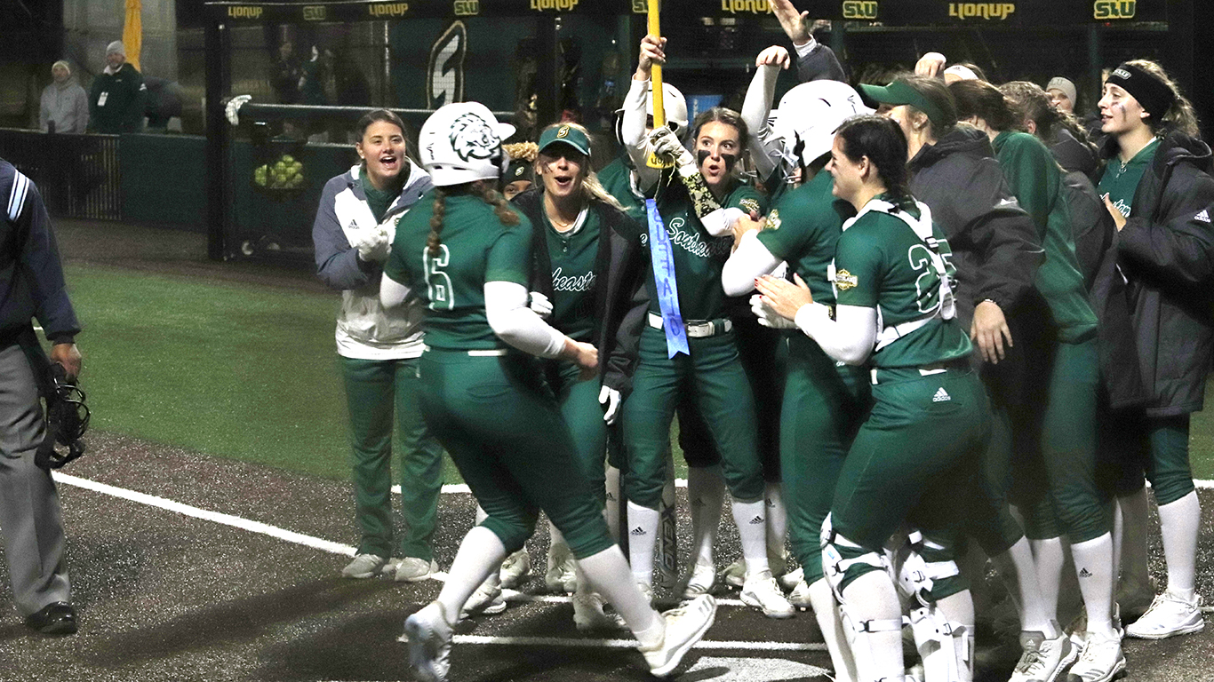Karlee Kraft, a sophomore pitcher/utility player, is met by her team at home plate after she hit her first home run of the season against Alabama State University.
