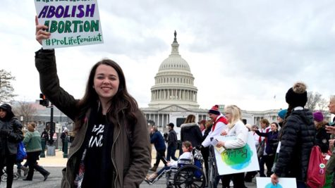 Taylor Gautreaux, coordinator for the Louisiana Students for Life trip, poses with a sign in front of the Capitol Building during March for Life 2020.