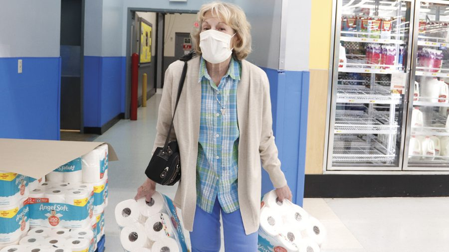 "A woman wearing a mask gathers items at Walmart, Monday, March 16, 2020, in Hammond. Toilet paper has become one of the much sought after items as many prepare for an extended ""quarantine"" at home."