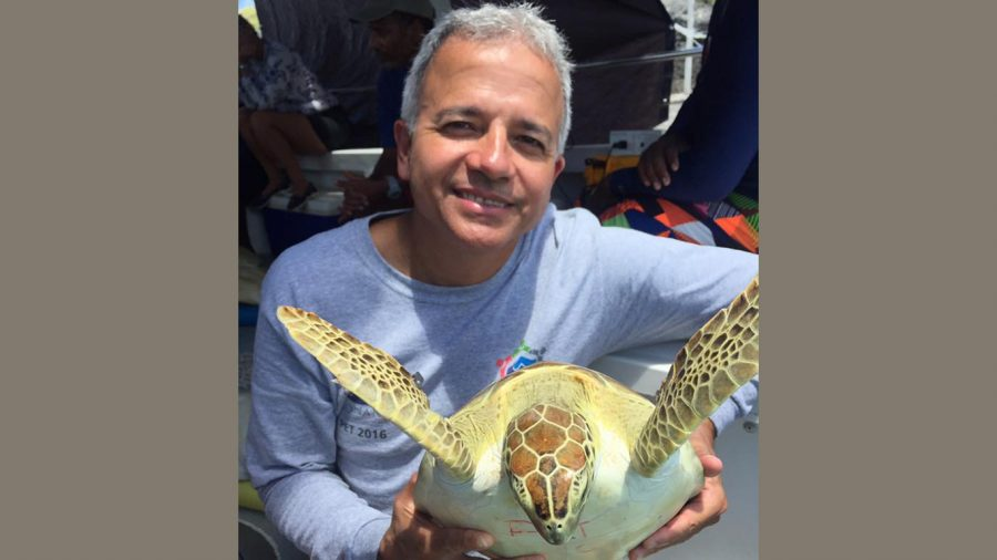 Dr.+Roldan+A.+Valverde%2C+a+professor+of+biology%2C+poses+for+a+picture+with+a+sea+turtle.+Valverde+researches+sea+turtles+and+also+works+as+the+scientific+director+of+the+Sea+Turtle+Conservancy+operating+in+Gainesville%2C+Florida.