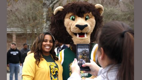 A university alumni poses with Roomie the Lion at the  2019 'Lion 4 Life' party. Being a member of the Alumni Association grants graduates access to a variety of social and networking events.