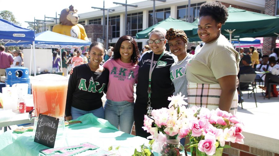 Members of Alpha Kappa Alpha sorority pose for a picture in front of their lemonade stand during Gumbo YaYa 2019.