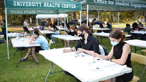 """Students gather in Friendship Circle for the university's """"Brush Away Your Stress"""" painting event as a part of Homecoming Week. Participants were provided with canvases, paint, water and paint brushes."""