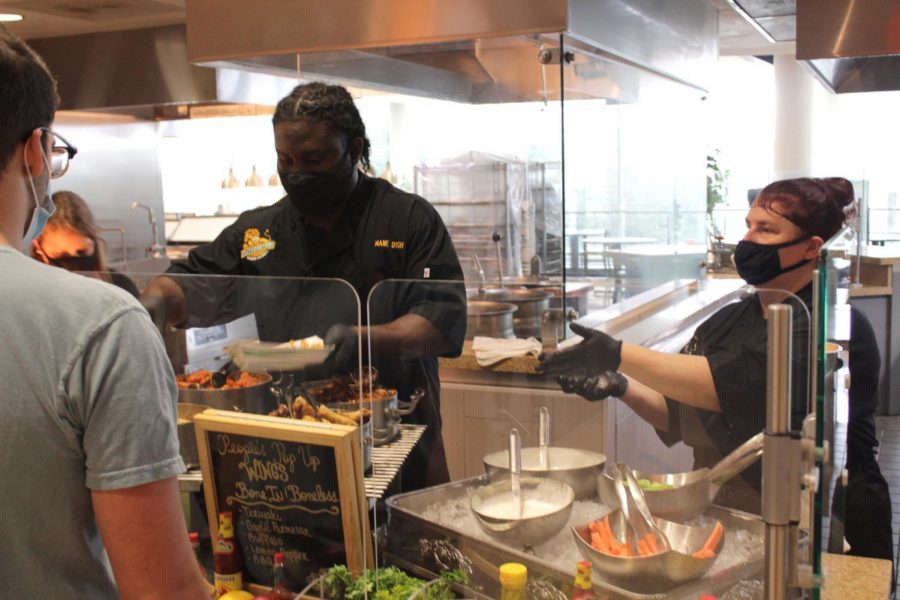 Mane Dish workers serve students buffalo wings with seasoned fries and their choice of sauces and vegetables.
