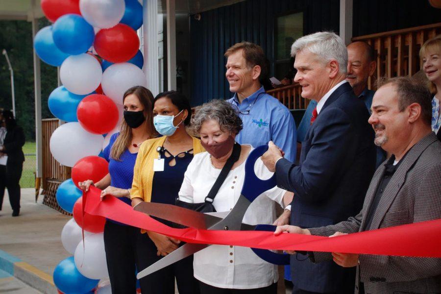 U.S. Sen. Bill Cassidy cuts the ceremonial ribbon alongside administrators of the Regina Coeli Child Development Center and other contributors of the new building.