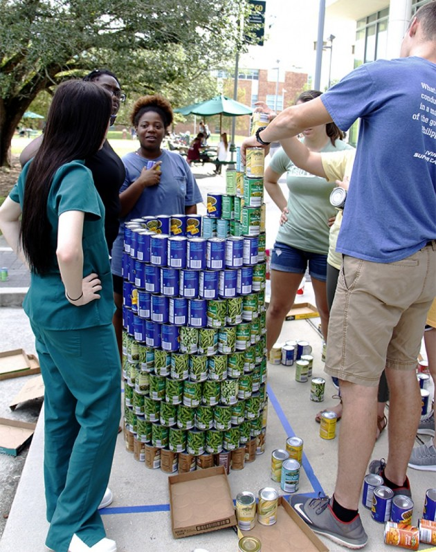 Students gather to build structures out of can goods