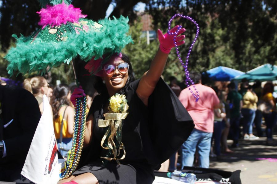 Member of the Homecoming Court Sydnie McClinton, a senior biological sciences major, throws beads during the Homecoming Parade.