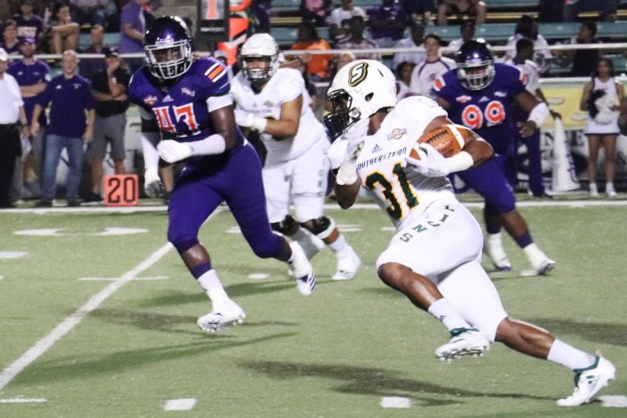 Taron Jones, a freshman running back, runs the ball down the field in the game against the Northwestern State University demons.