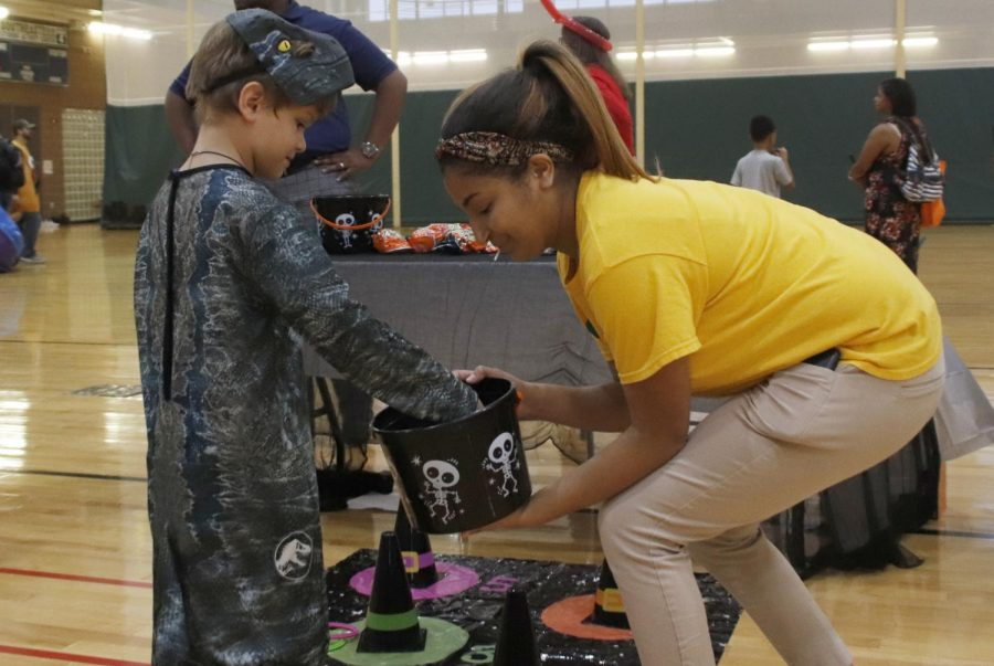 Leah+Cross%2C+a+junior+kinesiology+major%2C+hands+out+candy+for+%22Fall+Carnival.%22+Organizations+put+together+games+for+children+during+Halloween.+
