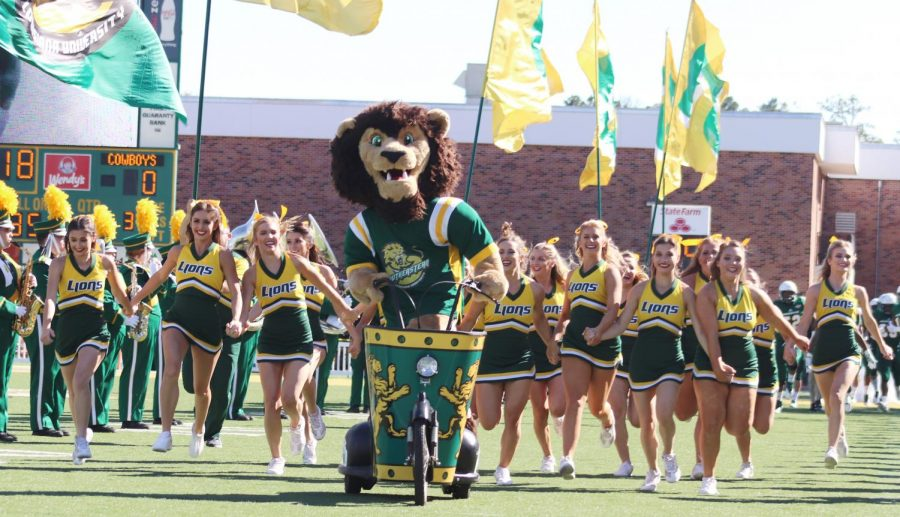 """Roomie rides out with the university cheerleaders before a home football game. Besides the spirit squads and mascot, home football games also include sponsorships like """"Our Mom of the Game."""""""