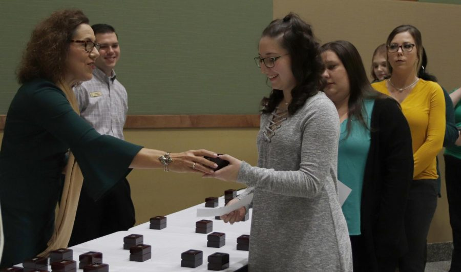 Graduating seniors accepts their university rings at ring ceremony ahead of commencement.