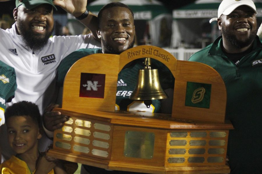 A player poses with the River Bell Classic trophy. The competition showcases the rivalry between the Lions and Colonels.
