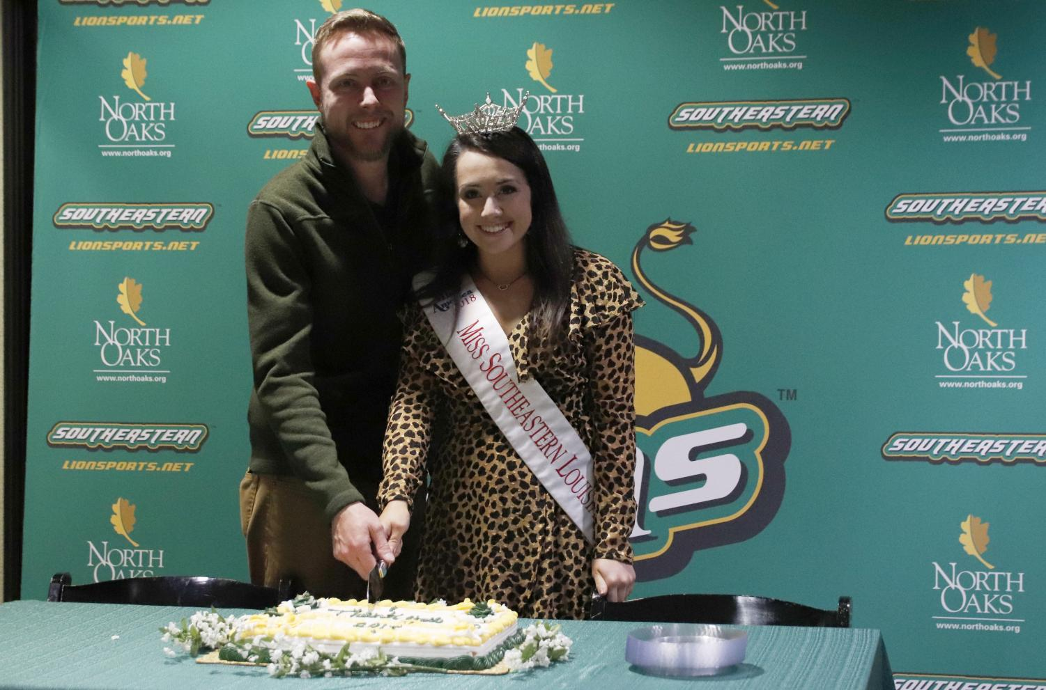 Alyssa Larose, a junior elementary education and special education major,  cuts the cake with Coordinator of Campus Activities Board Nick Elliott, celebrating her time as Miss Southeastern.
