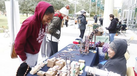 Iyania McClendon, a freshman kinesiology major, checks out wares at Reconnect's farmers market.
