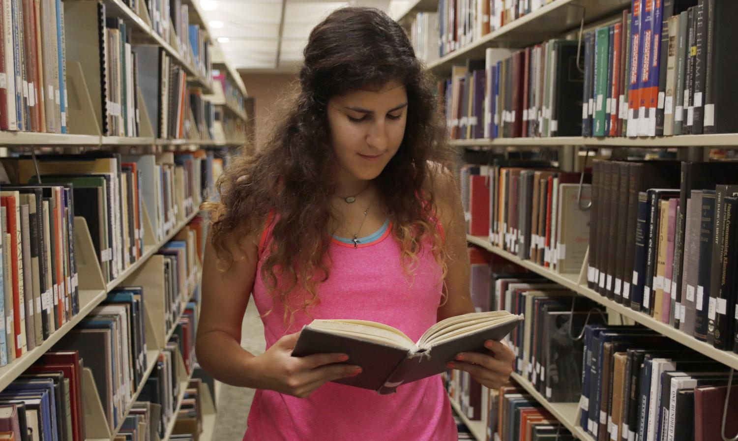 Nicole Zimmer, a senior biological sciences major, checks a book in the library. She has worked in the Sims Memorial Library for three years.