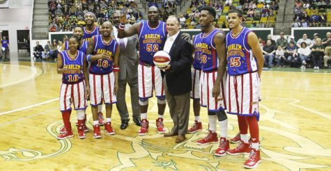 Jay Ladner, head coach of men's basketball, poses with the Harlem Globetrotters including former player Nate Lofton in the University Center. Ladner aims to help his players reach their full potential as a coach.