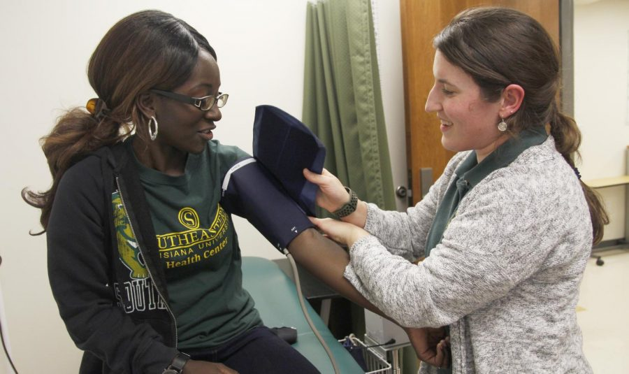 Eryn Brannagan, a senior health education and promotion major, right, performs a blood pressure check on a student. Taking patients' vitals is a part of her responsibilities as an intern with the University Health Center.