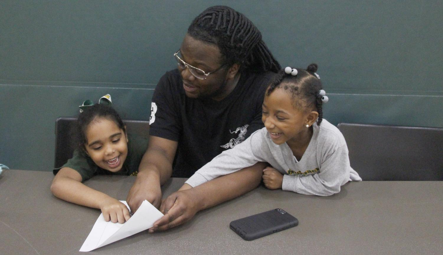 """Cameron Wood, a sophomore business administration major, helps two kindergartners with their homework. This contributes to the goals of the """"Rec Kids After School Program."""""""