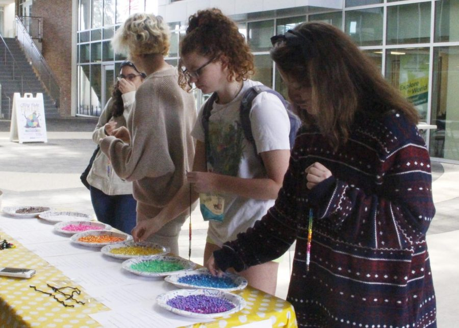 Students put beads on a string in association with privileges. The Southeastern Sociological Association held