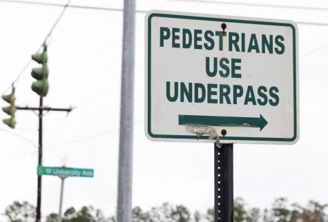 A sign on the corner of N General Pershing St. and W University Ave. directs pedestrians to utilize the underpass since there is not an established crosswalk running across W University Ave. University police have ticketed pedestrians for not abiding by this rule.