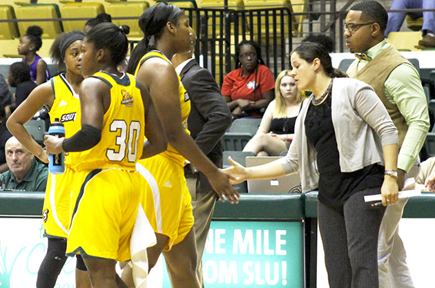 Head Coach Ayla Guzzardo interacts with players during a basketball game.