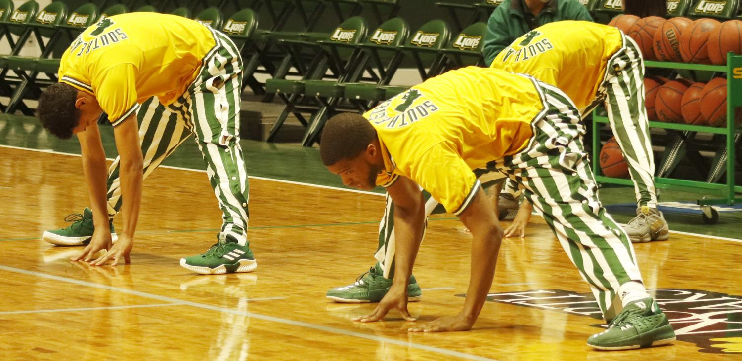 The men's basketball team stretches to warm up before the game against Sam Houston State University. Athletes are commonly viewed as role models to both athletes and non-athletes alike.