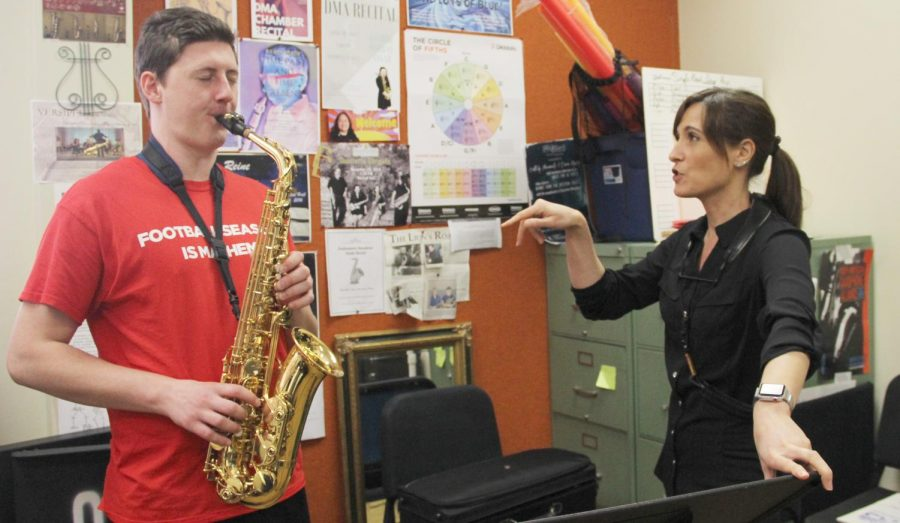 Brina Faciane, instructor of saxophone, teaches Austin Hynes, a junior music major, on the instrument.