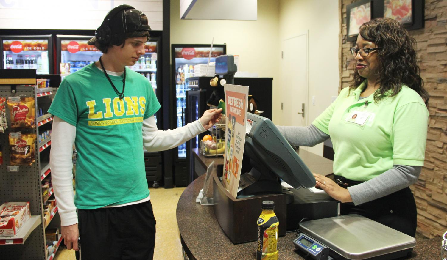 Evan McCann, a freshman information technology major, purchases food from Yolander Henderson in the Student Union Market. Lion's Lagniappe can be used on and off campus whereas Cub Cash only works on campus.
